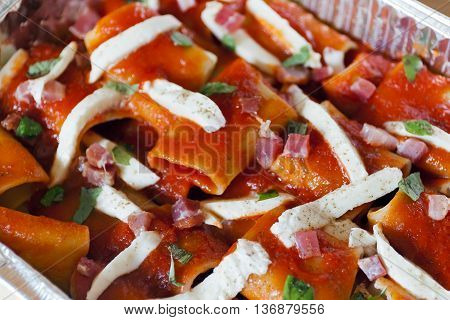 Paccheri baked pasta with tomato sauce mozzarella bacon and basil. Italian culinary specialties. Preparation raw before cooking in the oven. View from above.
