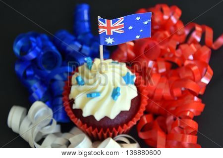 Happy Australia Day party food with red white and blue cupcake and Australian flag. Anzac Day. Celebration patriotism and holidays concept - close up of glazed muffin decorated with australian flag