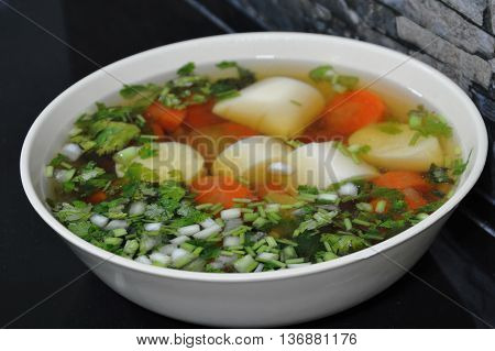 egg tofu and carrot chicken soup topping chop spring onion in bowl