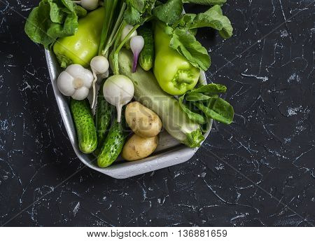 Fresh green and white vegetables - cucumbers peppers radish radish garlic onion potato zucchini on a dark background. Healthy vegetarian food