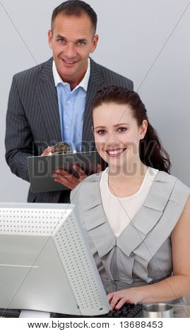 Charismatic manager and his employee smiling at the camera in the office