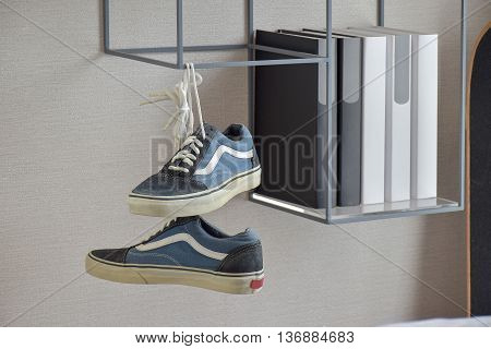 Pair Of Casual Blue Sneaker Shoes Hanging On Book Shelf At Home