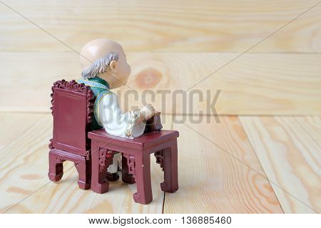 Happy Grandfather In Chinese Doll Is Listening Music On  Wood Background