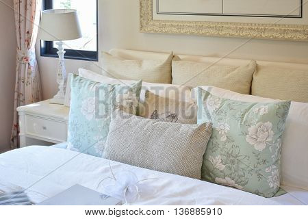 Vintage Bedroom Interior With Flower Pattern Pillow And Reading Lamp On White Bedside Table
