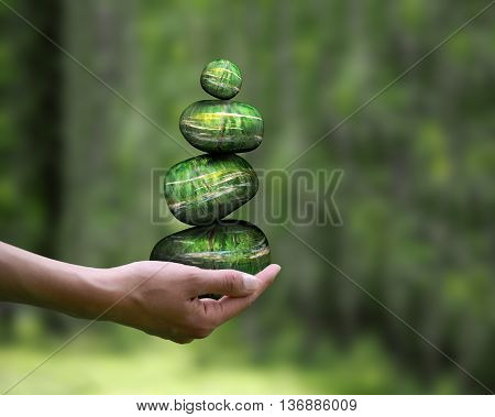 Pyramid of stones on a female hand. Natural green background. Concept - calm stability ecology environmental protection