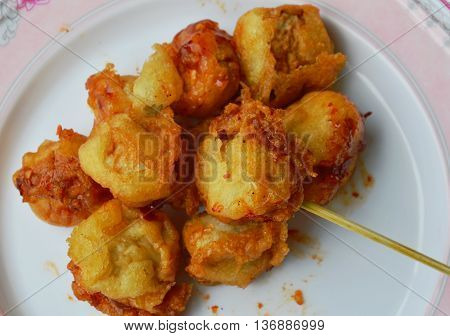 deep fried fish ball dressing chili sauce and wooden stick
