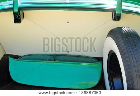 Classic car trunk with spare whitewall tire enclosed.