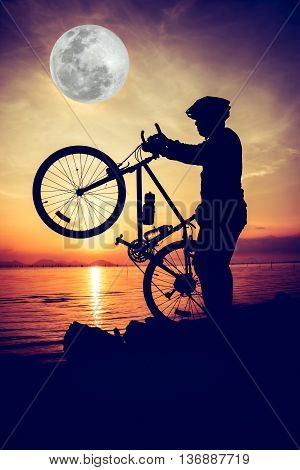 Silhouette of bicyclist in action enjoying the view at seaside on bright full moon sky background. Active outdoors lifestyle for healthy concept. Vignette and vintage picture style.