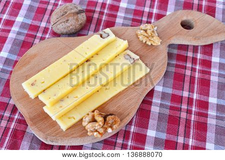 Sliced cheese on a wooden cutting board and burlap. Cheese with walnuts. Peeled walnuts