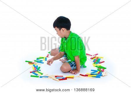 Happy asian child playing toy wood blocks isolated on white background. Strengthen the imagination of child. Studio shot.
