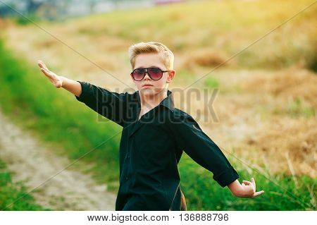 portrait of a little boy dancing in a field
