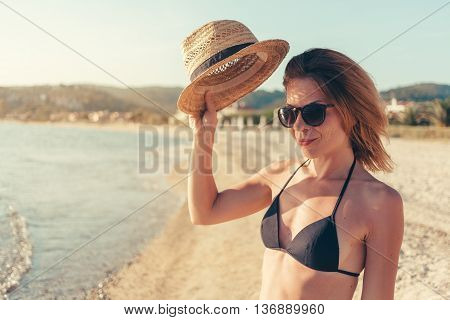 Smiling hipster woman outdoor portrait, holding her hat at the beach