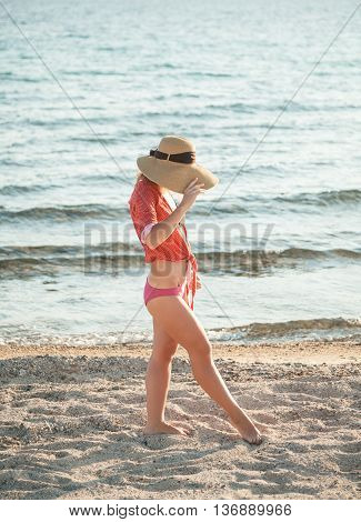 Hipster woman outdoor holding her hat at the beach
