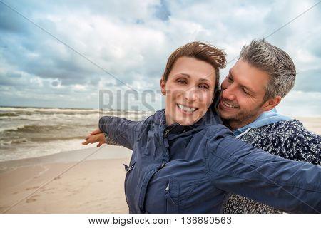 carefree boyfriend with girlfriend on windy coast