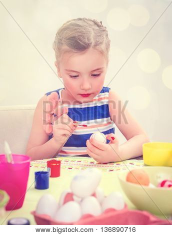 little girl coloring eggs at home