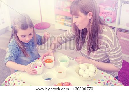 family coloring eggs at home