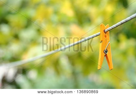 Yellow clothespin hanging on a rope in perspective on the background bokeh