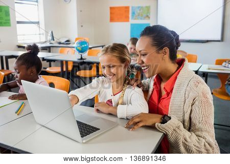 Teacher helping pupil with laptop in classroom