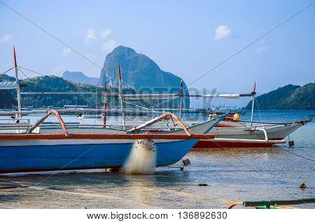 Colorful Philippines fishing boat on rocky shore near El Nido on Palawan island