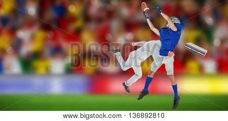 Businessman tackling a football player against blurry football pitch with crowd
