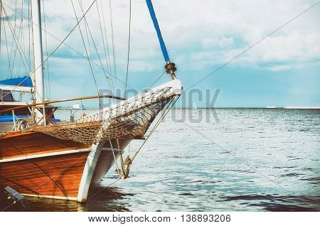 Boat moored at the sea pier. Wooden boat in the sea on a background of blue sky with clouds