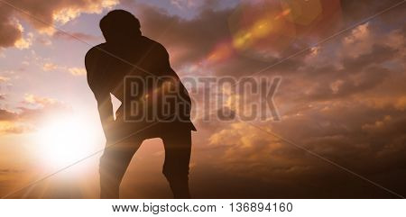 Athletic man resting with hands on knees against clouds