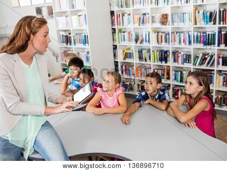 Teacher using tablet with pupils in library
