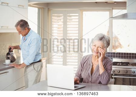 Senior woman talking on mobile phone with husband making tea in background at home