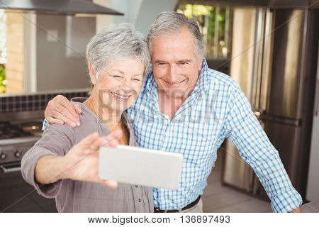 Cheerful senior couple taking selfie while standing in kitchen