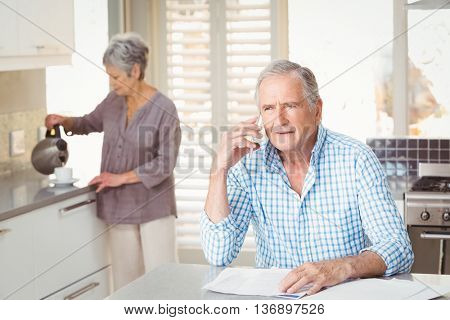 Senior man talking on mobile phone with wife making tea in background at home