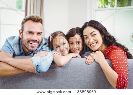 Portrait of happy family leaning on sofa at home