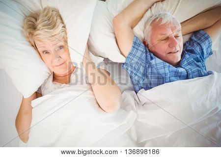 Portrait of woman covering ears from snoring husband on bed at home