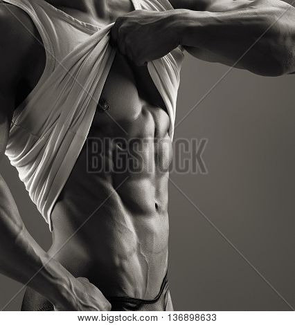 Muscular male lifts the shirt and showing chest and sixpack. Black and white image.