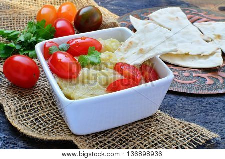 Eggplant dip with pita bread and grape tomatoes on rustic table setting
