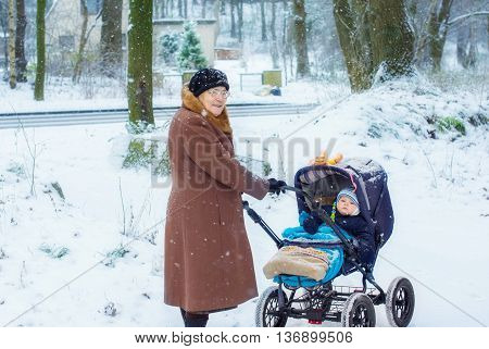 Great-grandmother walking with baby boy in pram during snowfall in winter. Happy family. Carefree childhood and generation.