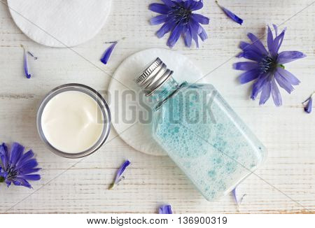 Facial cleansing tonic, moisturizer cream, cotton pads, blue chicory flowers. Botanical extracts, holistic skincare.