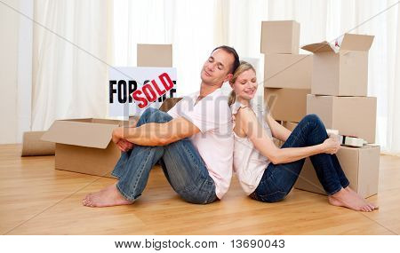 Young couple relaxing sitting on the floor while moving