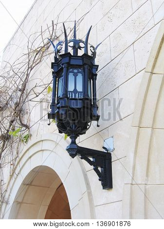 Street lamp on the wall of white stone