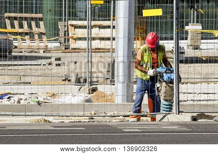 Builder worker at construction site. Completion of new office building in Konstitucijos prospect. Vilnius, Lithuania - June 29, 2016.