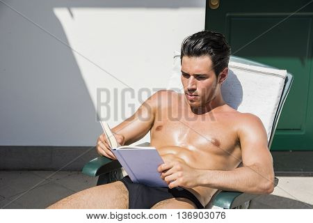 Shirtless Young Man Drying Off in Hot Sun Reading a Book, Muscular Man Wearing Bathing Suit Sunbathing on Beach Lounge Chair