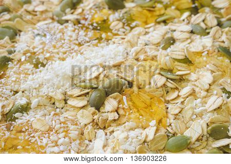 Muesli or cereals cooking background. Oat flakes organic seeds chip coconut and honey. Selective focus