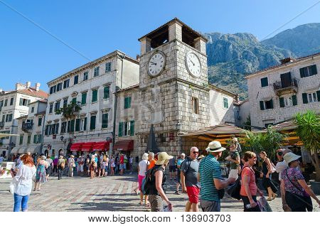 KOTOR MONTENEGRO - SEPTEMBER 22 2015: Unidentified tourists are walking near ancient Clock tower on Plaza of Oruzja in Old Town of Kotor Montenegro
