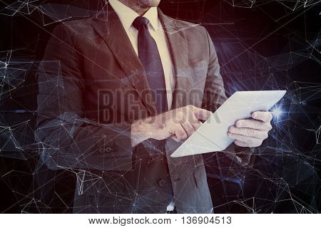 Businessman using his tablet pc against black background with shiny lines