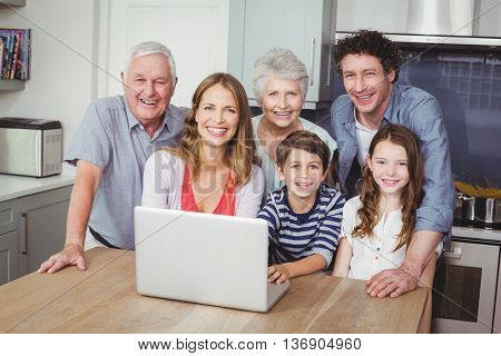 Portrait of happy family using laptop on table in kitchen at home