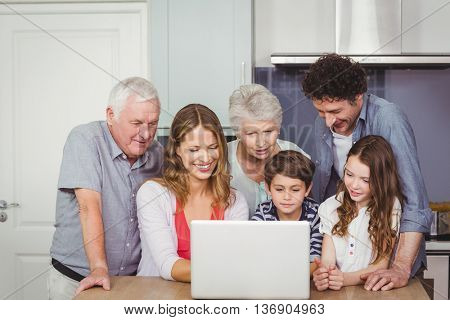Family looking into laptop on table in kitchen at home