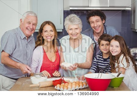 Portrait of smiling happy family cooking food in kitchen at home