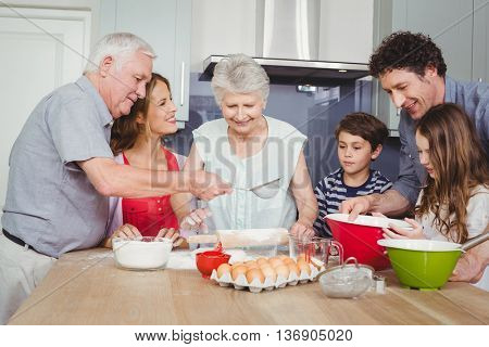 Smiling family preparing food in kitchen at home