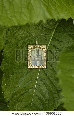 Saint Nicholas icon on big green leaf close up
