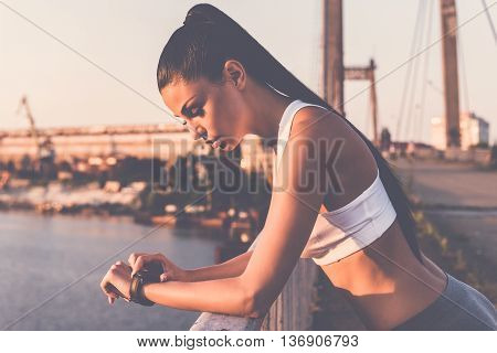Checking the time. Beautiful young woman in sports clothing looking at her wristwatch while standing on the bridge