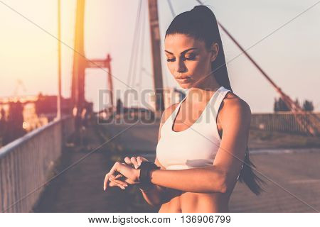 Setting smartwatch for running. Beautiful young woman in sports clothing looking at her wristwatch while standing on the bridge